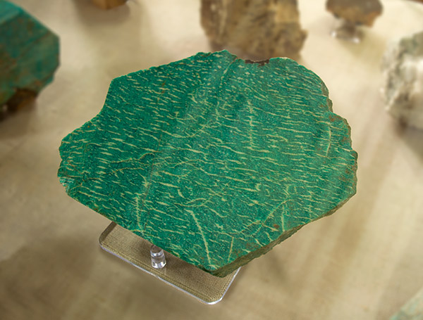 polished amazonite mineral in a museum display cabinet