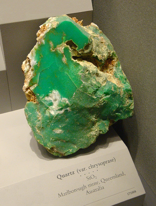 large rough chrysoprase mineral in a museum display cabinet