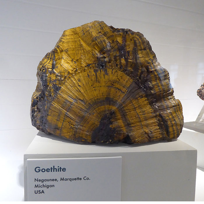 large goethite mineral on display in a museum display cabinet