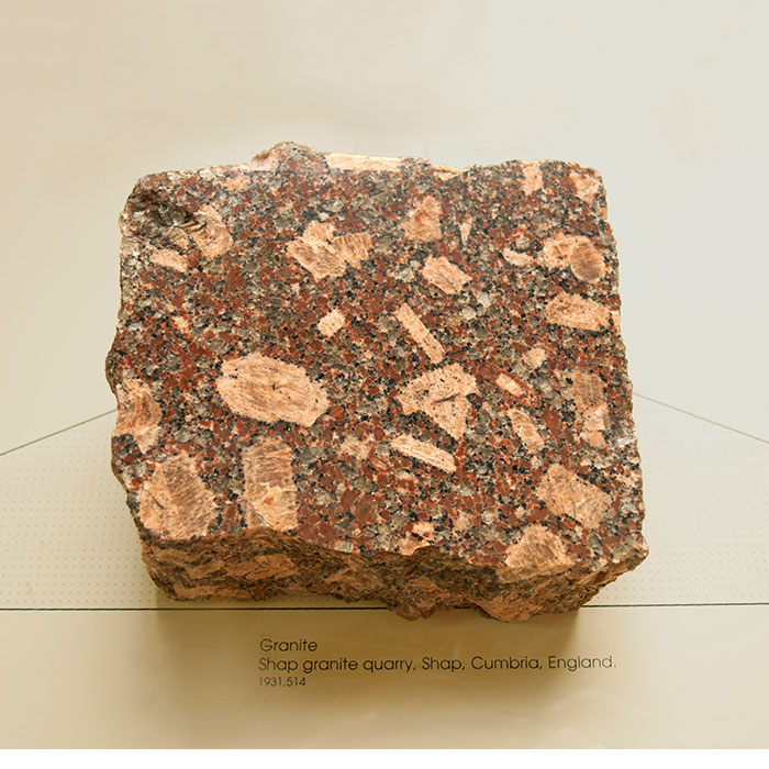 square chunk of granite stone on display in a museum display cabinet