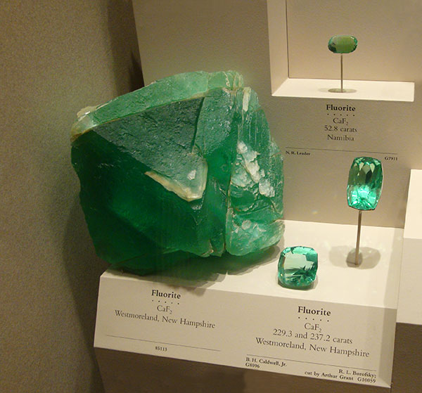 large cube-like shape of the mineral green fluorite in a museum display cabinet