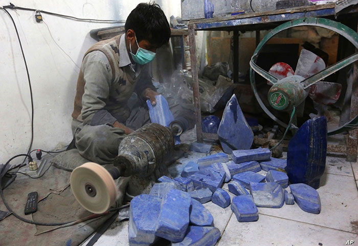 Afghan man sitting on the floor polishing lapis lazuli with a stone polishing machine