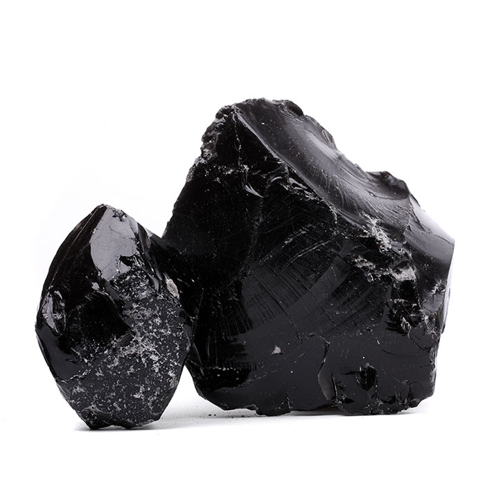 two pieces of natural black obsidian side by side isolated on a white background