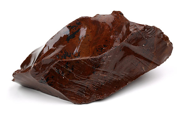 piece of red obsidian volcanic glass isolated on a white background