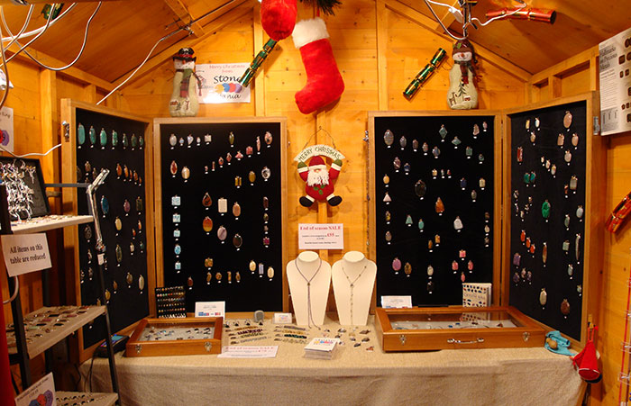 Gemstone jewellery being sold by Stone Mania inside a traditional wooden hut at a Christmas Market