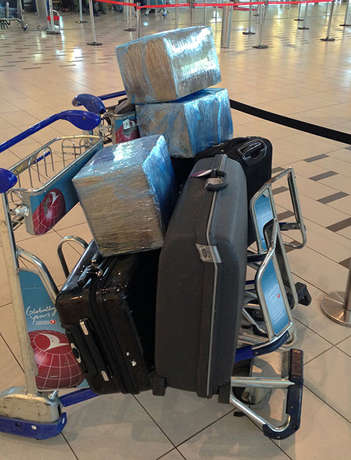 two airport trolleys with three cases and three boxes on top
