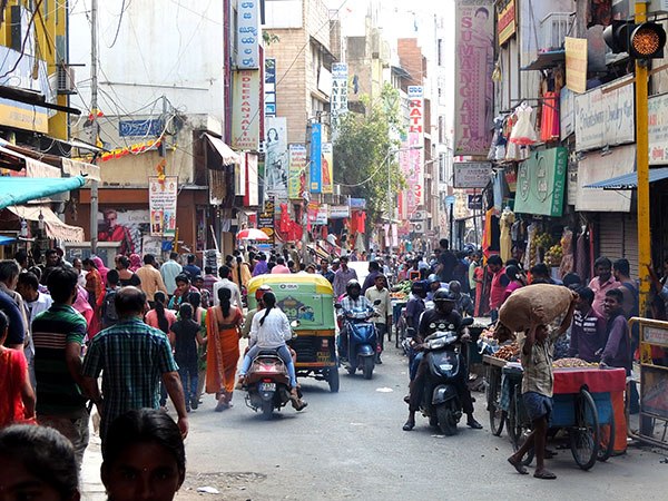 busy street market in India full of people, motorbikes and motorised rickshaws