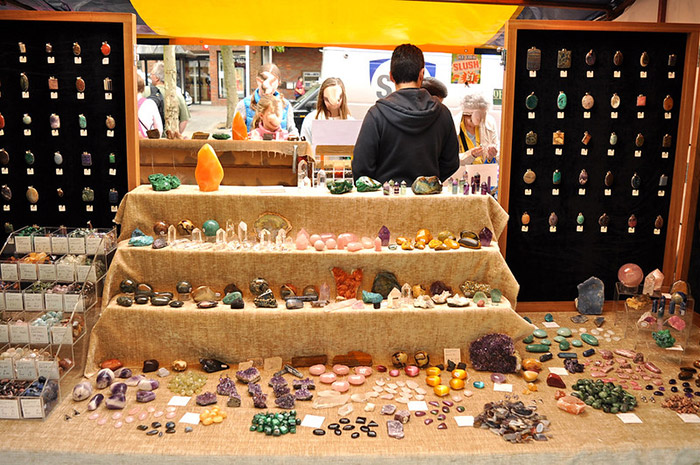 Market stall selling crystals rocks minerals gemstones. People browsing on the back counter with stall holder watching