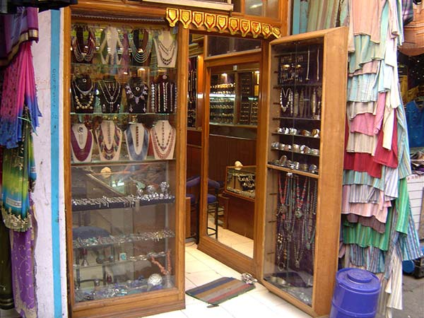 front of shop in a street market in India. The window is full of jewellery