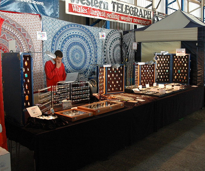 Owner of Stone Mania on his retail stand. Display boards with necklace pendants can be seen plus other items of jewellery