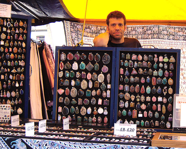 Owner of Stone Mania looking over a display board of gemstone pendants on his market stall
