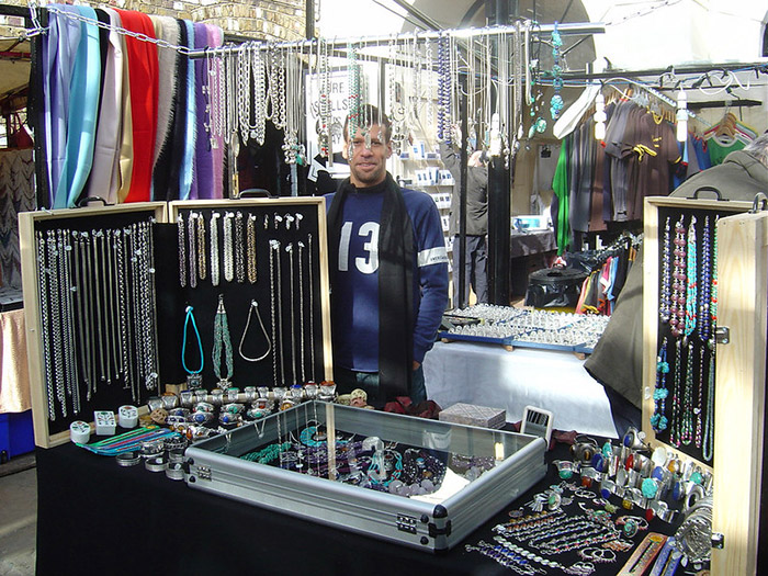 Owner of Stone Mania standing behind his market stall. Surrounded by silver and gemstone jewellery