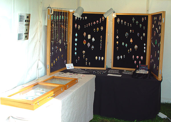 retail stand with display boards of gemstone necklace pendants plus display cases of jewellery