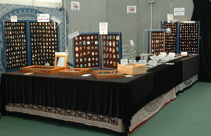Retail stand with display boards of gemstone pendants. Other items of jewellery are laid out on the counter
