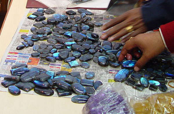 The hands of two men selecting labradorite cabochons from a table