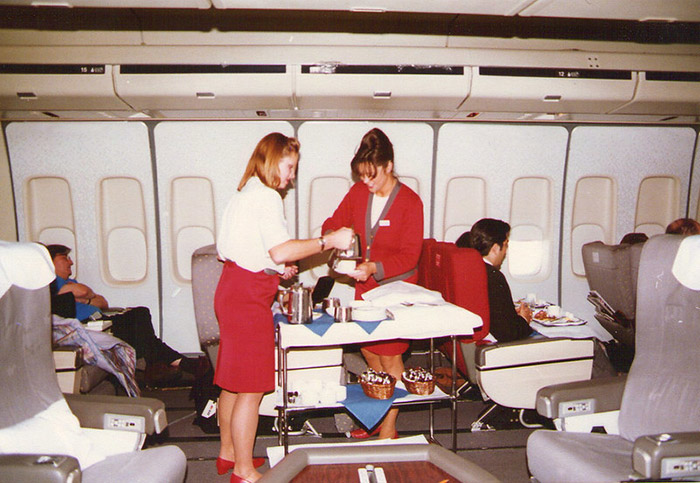 two virgin atlantic stewardesses serving afternoon tea from a trolley in first class