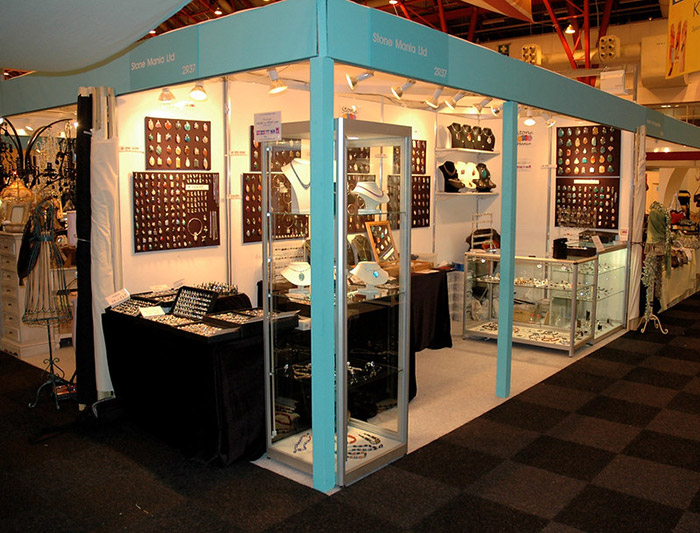 Retail stand of Stone Mania at Ideal Home Show. Display boards of gemstone pendants and counters are inside