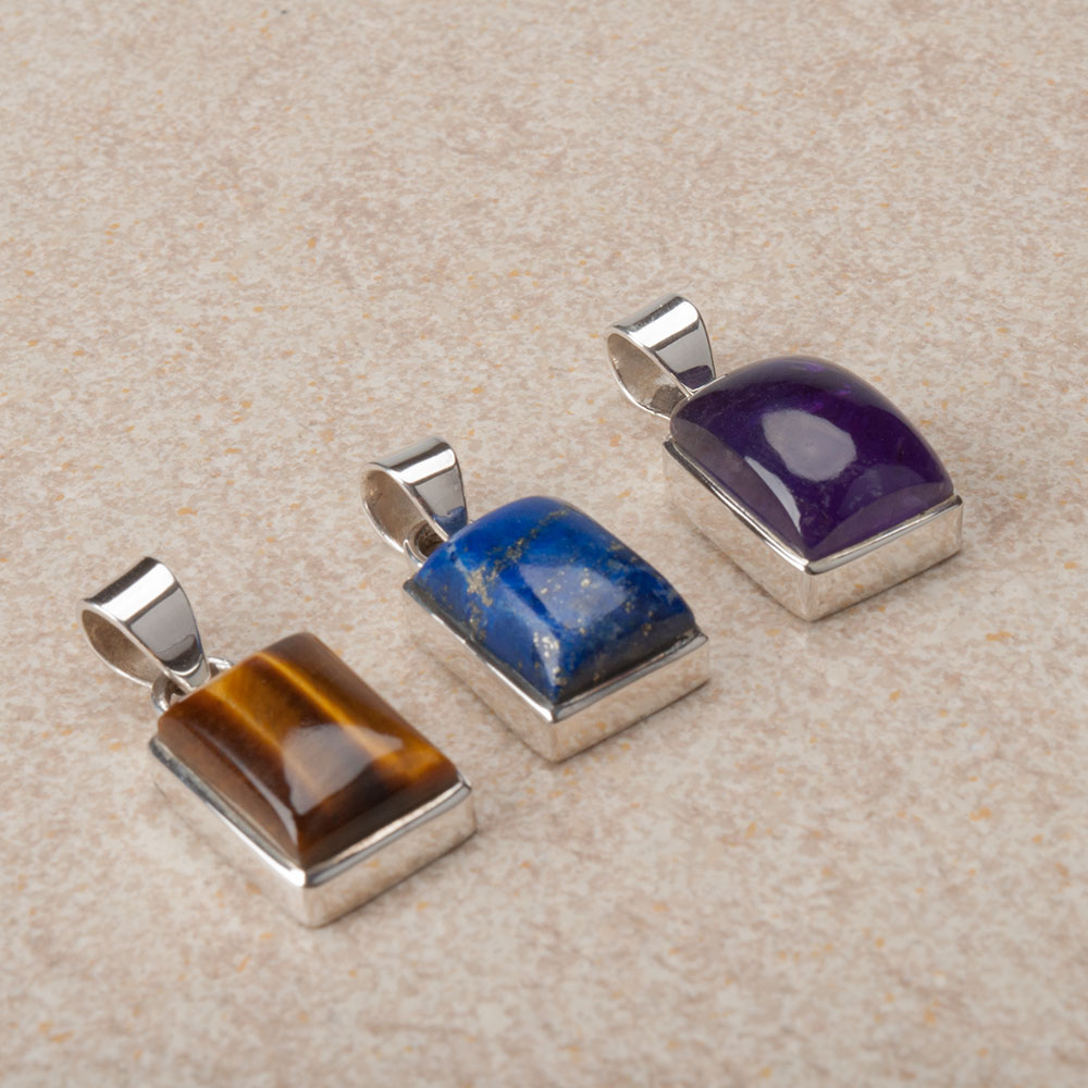 three sterling silver pendants each featuring a single gemstone