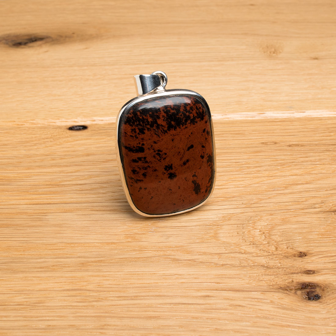 red obsidian gemstone mounted as a ladies pendant
