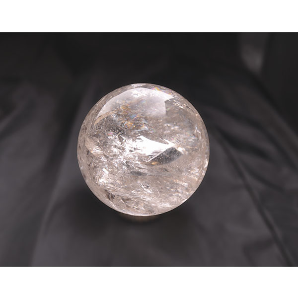 round quartz crystal ball with a glass-like surface and visible crystallization on the inside
