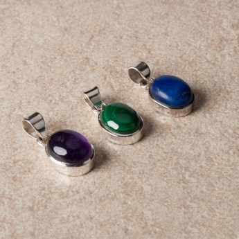 three small oval shaped gemstone pendants crafted in sterling silver
