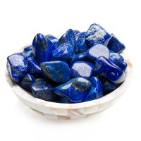 mother of pearl dish filled with large blue coloured lapis lazuli tumbled stones