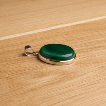 oval shaped sterling silver pendant featuring a malachite cabochon gemstone
