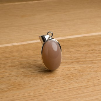 oval shaped moonstone pendant featuring a bulbous gemstone. Sterling silver setting