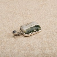 small ocean jasper cabochon mounted as a ladies pendant in a sterling silver setting