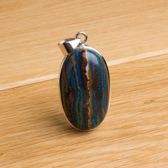 oval shaped rainbow calsilica stone mounted as a ladies pendant in sterling silver