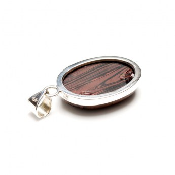 red tigers eye polished cabochon mounted as a ladies pendant in sterling silver