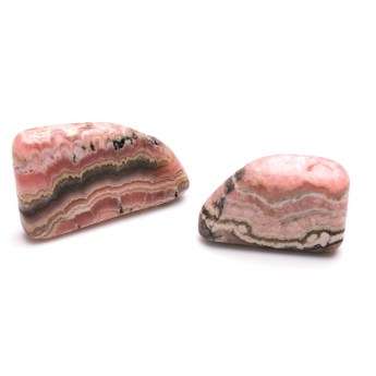 three pinkish red coloured rhodochrosite stones