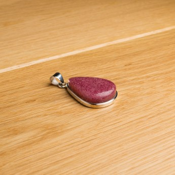 pear shaped sterling silver pendant featuring a polished rhodonite cabochon