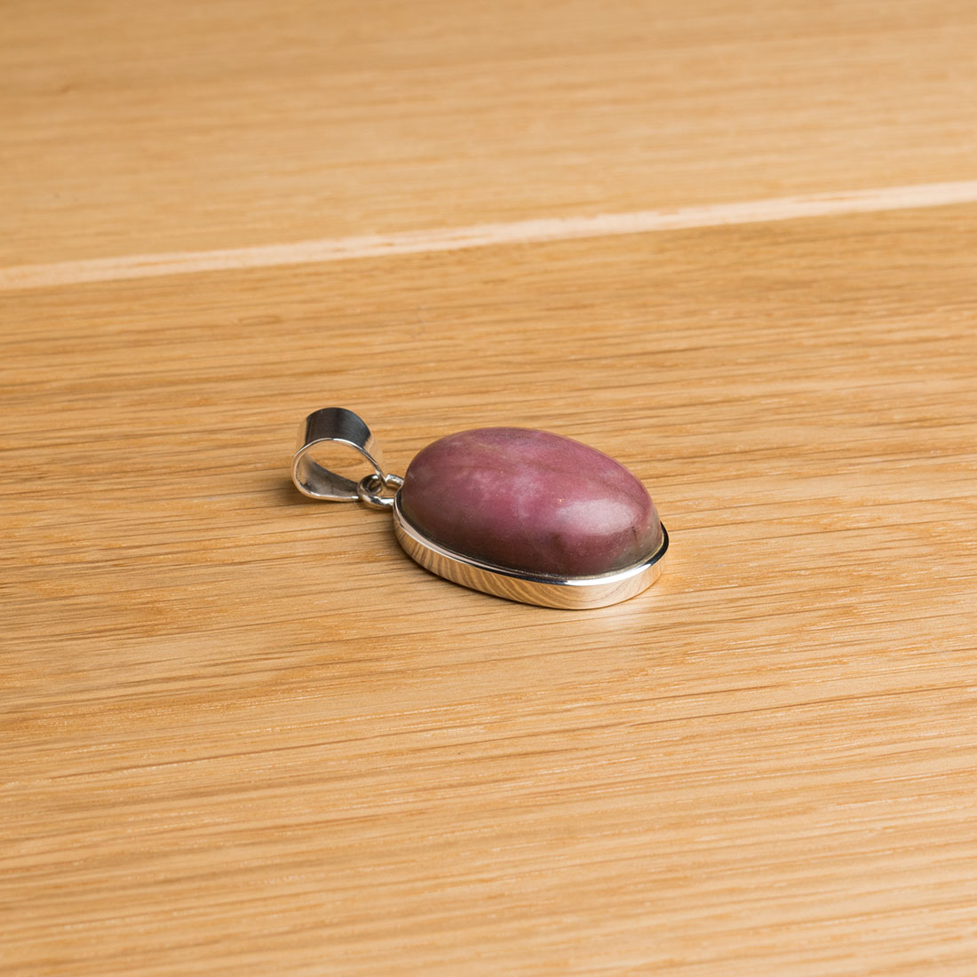 oval shaped sterling silver pendant featuring a chunky rhodonite gemstone