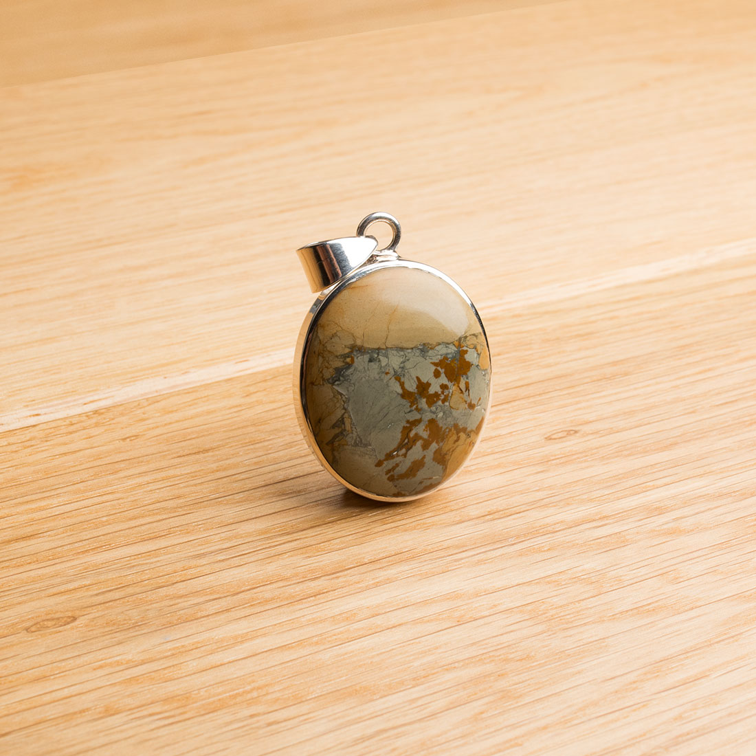 oval shaped sterling silver pendant featuring a polished scenic jasper gemstone