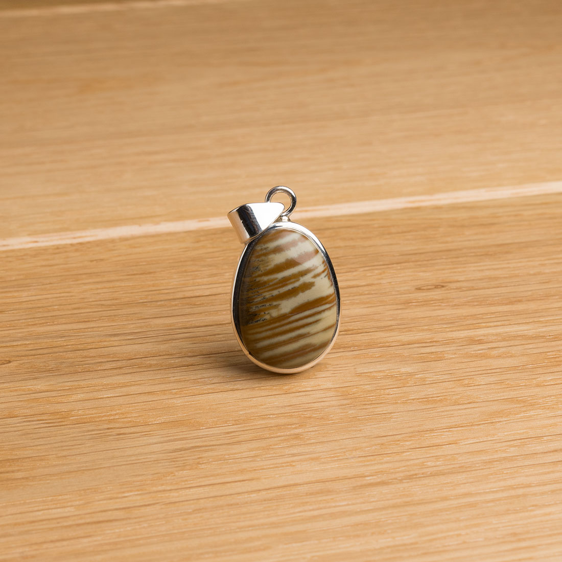 small oval shaped sterling silver pendant featuring a polished jasper cabochon